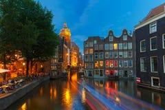 Nattstadssikt av den Amsterdam kanalen, kyrkan och bron Royaltyfria Foton