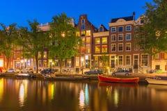 Nattstadssikt av den Amsterdam kanalen med holländare royaltyfria foton