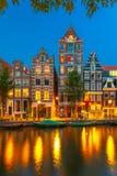 Nattstadssikt av den Amsterdam kanalen med holländska hus royaltyfria bilder