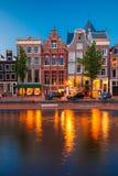 Nattstadssikt av den Amsterdam kanalen med holländska hus Arkivfoton