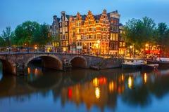 Nattstadssikt av den Amsterdam kanalen och bron fotografering för bildbyråer