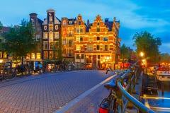 Nattstadssikt av den Amsterdam kanalen och bron Arkivbild