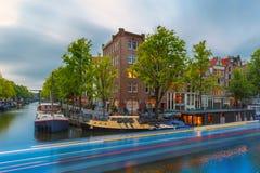 Nattstadssikt av den Amsterdam kanalen och det lysande spåret från bet Royaltyfria Foton