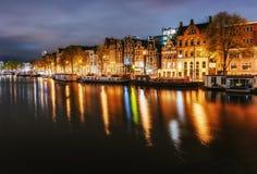 Nattstadssikt av den Amsterdam kanalen, typiska holländarehus och boaen royaltyfri bild