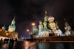 Nattstadssikten av MoskvaKreml, den Sanka domkyrkan för basilika` s och den röda fyrkanten på aftonen övervintrar snöfall i Moskv royaltyfri foto