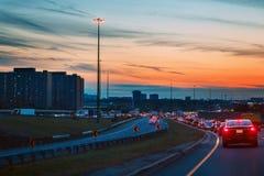 Natttrafik, bilar på huvudvägvägen på solnedgångaftonnatt i upptagen stad arkivbild