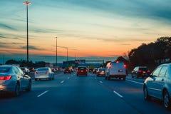 Natttrafik, bilar på huvudvägvägen på solnedgångaftonnatt i upptagen stad arkivfoton