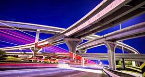 Natttrafik med ljus skuggar på huvudvägutbyte Arkivbilder