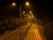 Natttrafikljus Den Timelapse videoen av den mörka huvudvägvägen med gör ljusare lampor lager videofilmer