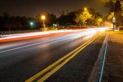 Nattväg i staden med bilen som ljuset skuggar Arkivfoto