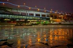 Nattvintercityscape med bron ovanför Moskvafloden i is arkivfoton