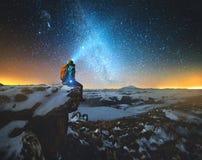 Nattvinterlandskapet en man med en ryggsäck och en lykta på hans huvud sitter på vaggar i bergen i vinter mot arkivfoto
