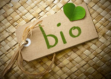 Natual cardboard label with the word bio. Natural cardboard label with the word bio handwritten on it plus a green clover petal Stock Images