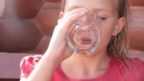 Natur des kleinen Mädchens trinkt Wasser von einem Glas stock video