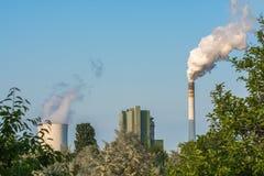 Natur under påverkan av den närliggande kraftverket med den tungt rökiga lampglaset royaltyfria bilder