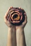 Natura d'offerta Due mani e un carciofo sono aumentato Fotografia Stock