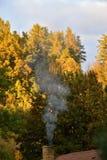 Natura di autunno Camini fumosi Sugli alberi il sole splende nuvoloso Immagini Stock Libere da Diritti