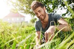 Natura ed ambiente Il giovane buio ha pelato il gardenist barbuto che spende il tempo in giardino vicino alla casa di campagna Ta Fotografia Stock