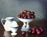 Natura morta, ciliege, brocca di latte, uovo sodo su una tavola di legno Fotografia Stock