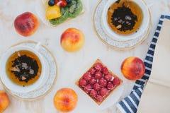 Natura morta con due tazze di tè in tazze di un'annata e due crostate con la frutta fresca su un fondo d'annata bianco Immagine Stock