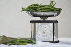 Natura morta con i fagiolini e la scala freschi dell'equilibrio fotografia stock