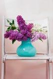 Natura morta con i fiori lilla in turchese del vaso disposto su un fondo di legno Fotografie Stock Libere da Diritti