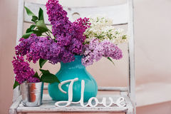 Natura morta con i fiori lilla in turchese del vaso disposto su un fondo di legno Immagine Stock Libera da Diritti