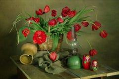 Natura morta con i tulipani rossi in un canestro su un fondo marrone fotografia stock libera da diritti
