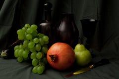 Natura morta con il coltello dell'uva, del melograno, della vite e dell'oro Fotografie Stock