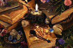 Natura morta con il libro antico della strega, la candela nera e gli oggetti rituali immagine stock libera da diritti