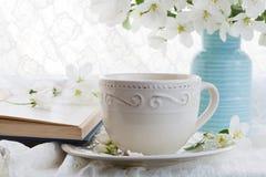 Natura morta con il ramo della tazza e del fiore di tè Fotografia Stock