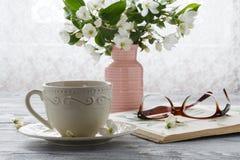 Natura morta con il ramo della tazza e del fiore di tè Immagine Stock