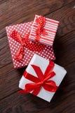 Natura morta con il regalo di festa in piccola scatola dei colori rossa con il nastro e l'arco su fondo di legno, vista superiore Immagine Stock