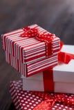 Natura morta con il regalo di festa in piccola scatola dei colori rossa con il nastro e l'arco su fondo di legno, vista superiore Fotografia Stock
