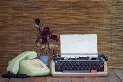 Natura morta con il vecchio telefono della macchina da scrivere con i fiori rosa asciutti Fotografia Stock Libera da Diritti