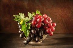 Natura morta con l'uva nella tazza di rame antica della latta Immagini Stock Libere da Diritti