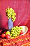 Natura morta con la bottiglia e la frutta: pesche, mele ed uva nello stile orientale immagini stock