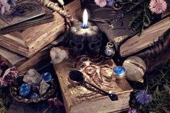 Natura morta con la candela spaventosa del nero del cranio, oggetti del libro della strega e di rituale alla luce mistica fotografie stock libere da diritti