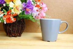 Natura morta con la tazza da caffè ed i fiori in vaso su una tavola di legno Fotografie Stock Libere da Diritti