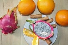 Natura morta con le arance, il dragonfruit ed i biscotti Fotografia Stock Libera da Diritti