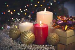 Natura morta con le candele brucianti, le decorazioni di Natale e un contenitore di regalo Fotografia Stock Libera da Diritti