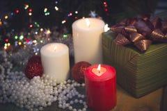 Natura morta con le candele brucianti, le decorazioni di Natale e un contenitore di regalo Fotografia Stock