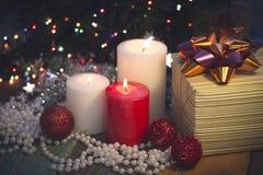 Natura morta con le candele brucianti, le decorazioni di Natale e un contenitore di regalo fotografie stock