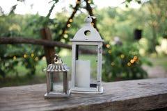 Natura morta con le candele in lampade e ghirlanda illuminata su un fondo Fotografia Stock Libera da Diritti