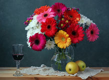 Natura morta con le margherite del Transvaal, le mele ed il vino rosso Fotografie Stock