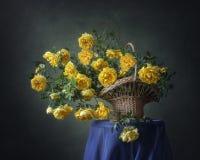 Natura morta con le rose selvatiche di giallo del canestro fotografia stock