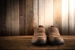 Natura morta con le scarpe degli uomini sul ripiano del tavolo di legno contro il wa di lerciume Immagini Stock