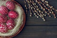Natura morta con Pysanka, uova di Pasqua decorate, su di legno nero Fotografia Stock