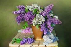 Natura morta con un mazzo del lillà di fioritura su un fondo verde fotografia stock