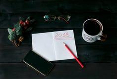Natura morta con un taccuino con un'iscrizione rossa 2018, una tazza di caffè fotografie stock